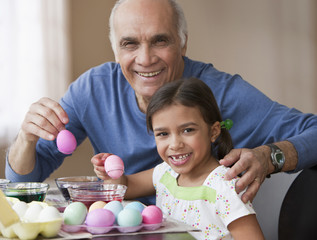 Grandfather and granddaughter dying Easter eggs