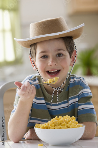 Caucasian boy eating macaroni and cheese and wearing cowboy hat