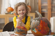 Caucasian girl painting pumpkins