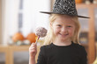 Caucasian girl in witch Halloween costume holding candy apple