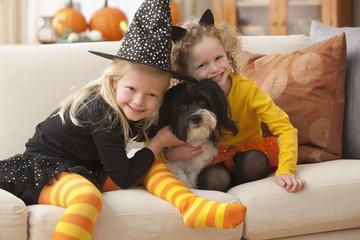 Caucasian girls in Halloween costumes hugging dog