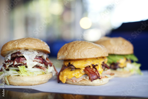 Various indulgent cheeseburgers in diner
