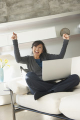 Chinese woman sitting with laptop cheering