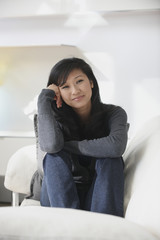 Smiling Chinese woman sitting on sofa