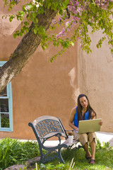 Hispanic woman sitting on park bench using laptop