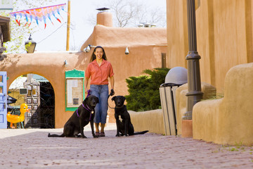 Hispanic woman walking dogs in town