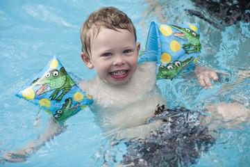Caucasian boy swimming in swimming pool