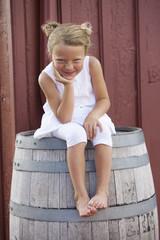 Grinning Caucasian girl sitting on barrel