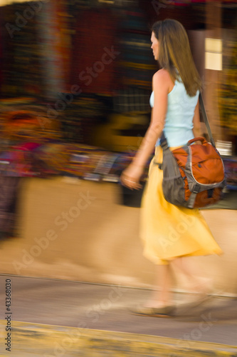 Hispanic woman walking on sidewalk