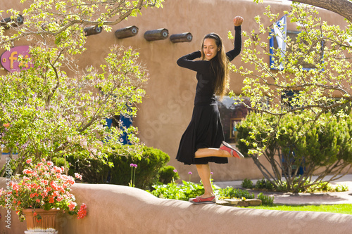 Hispanic woman dancing on wall