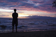 Caucasian man standing on beach viewing sunset