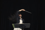 Mixed race conductor pointing baton