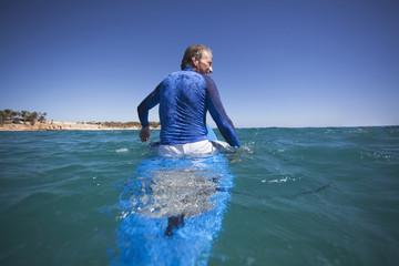 Caucasian man floating on surfboard