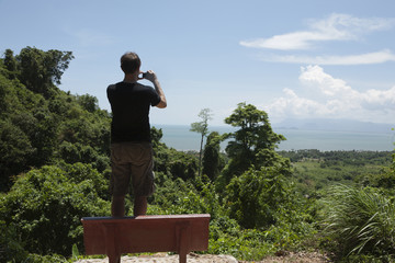 Caucasian man taking photograph of remote area