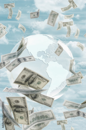 Globe and money floating in sky