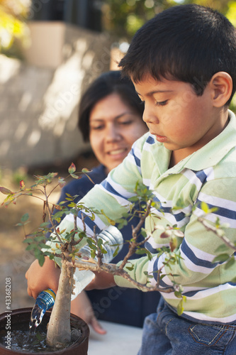 Hispanic mother and son gardening together