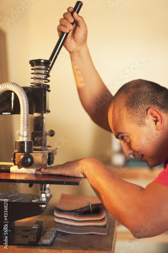 Hispanic man operating book-binding machine