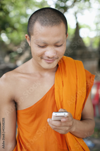 Cambodian monk text messaging on cell phone