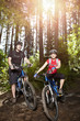 Couple riding mountain bike in forest