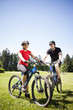 Couple riding mountain bikes in field