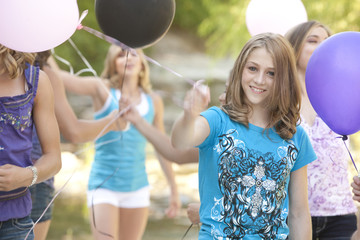 Teenage friends holding balloons