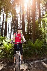 Hispanic woman riding mountain bike in forest