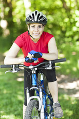 Hispanic woman riding mountain bike in forest
