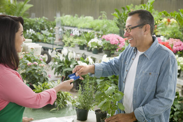 Customer handing florist his credit card
