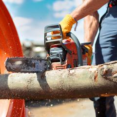 Arbeiter schneidet mit Kettensäge
