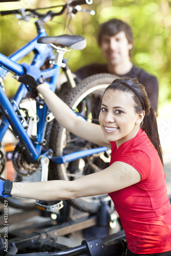 Couple loading mountain bikes on rack