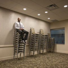Mixed race businessman sitting on stack of chairs