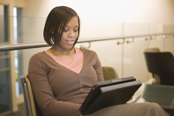 African American businesswoman using digital tablet in hotel lobby