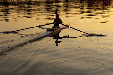 Person rowing sculling boat on river