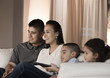Hispanic family sitting on sofa watching television
