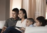 Hispanic family sitting on sofa watching television
