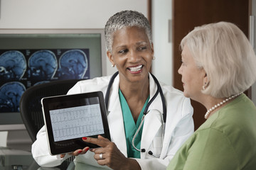 Doctor using digital tablet while talking to patient