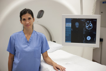 Hispanic nurse standing near MRI scanner in hospital