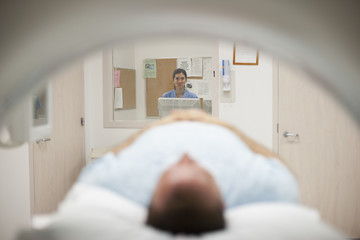 Nurse watching patient on MRI scanner in hospital