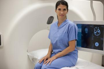 Hispanic nurse sitting on MRI scanner in hospital