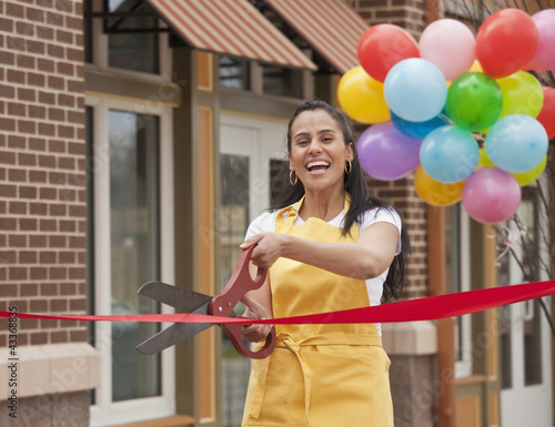 Excited business owner cutting ribbon on grand opening