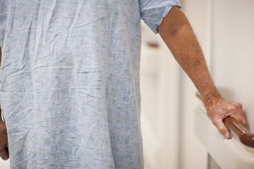 Caucasian patient leaning on railing in hospital