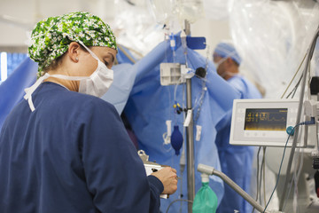 Nurse viewing monitors in operating room