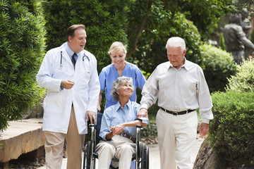 Doctor and nurse walking with patient in wheelchair