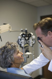 Eye doctor checking woman's eyes