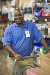Man standing in warehouse with inventory and hand cart