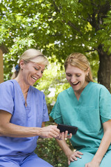 Caucasian nurses looking at cell phone