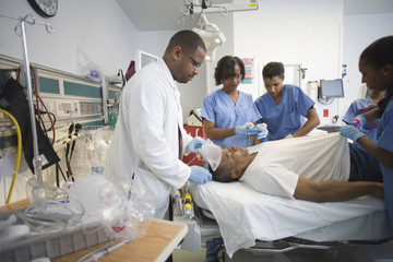 Doctors and nurses working on patient in emergency room