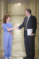 Doctor and businessman shaking hands in hospital corridor