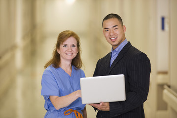 Doctor and businessman standing with laptop in hospital corridor