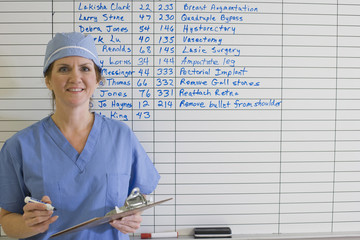 Doctor standing next to schedule whiteboard in hospital